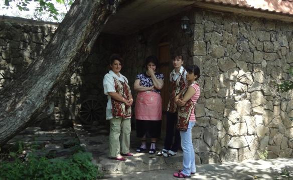 Women of Garni Village stand talking.