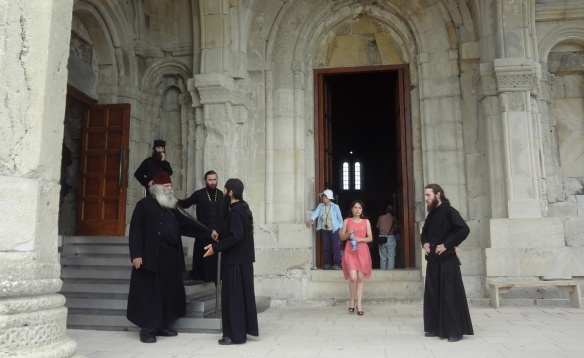 High priest and monks in front of the church