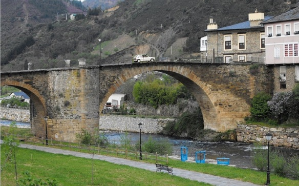 Medieval stone bridge arched across the river Burbia.