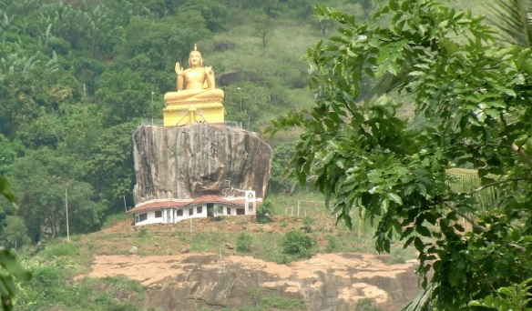 Golden Buddha statue on the highest point of Aluvihāra at the hillside.