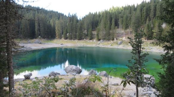 Emerald green water of the Carezza Lake