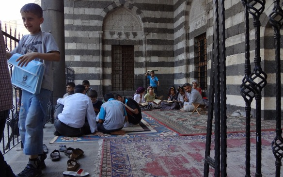 Children are studying the Koran outside the mosque.