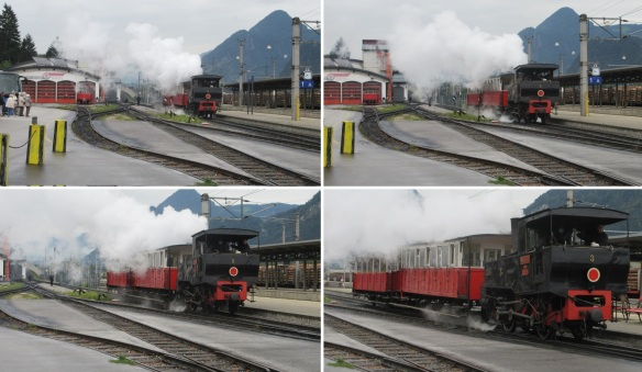 A steam locomotive was coming over carrying two passenger cars.