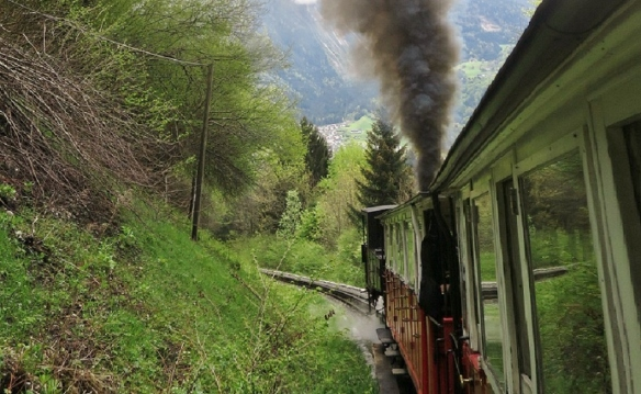The little steam locomotive went up a steep hill pushing the passenger cars.