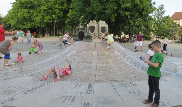Kids are playing on the 0 km stone.
