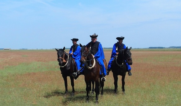 Three riding Magyars appear. Splendid horses!